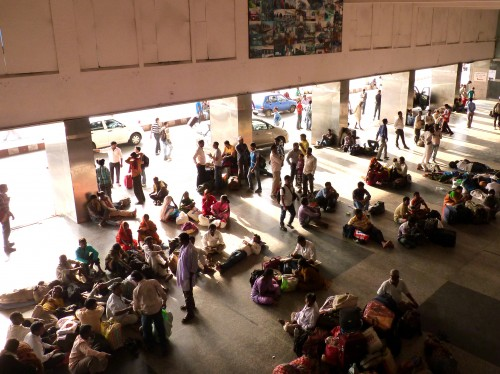 At New Delhi Railway Station groups sit around or sleep on the floor until it's time for their train