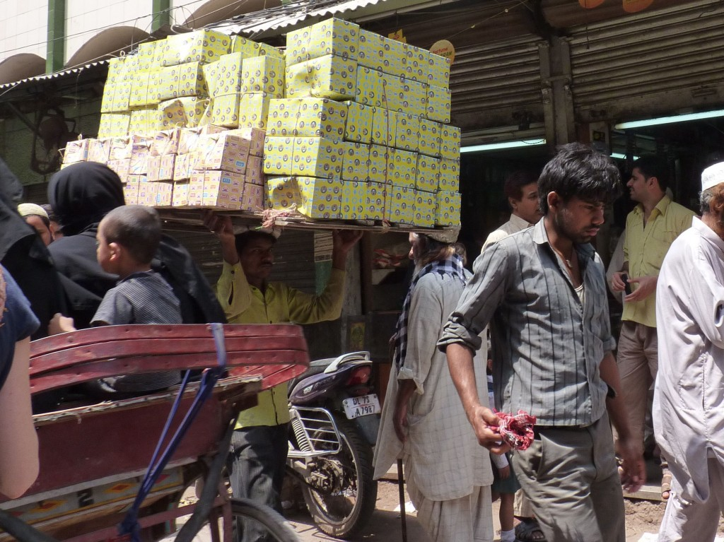 A man balances dozens of boxes on his head while moving through Old Delhi Bazaar
