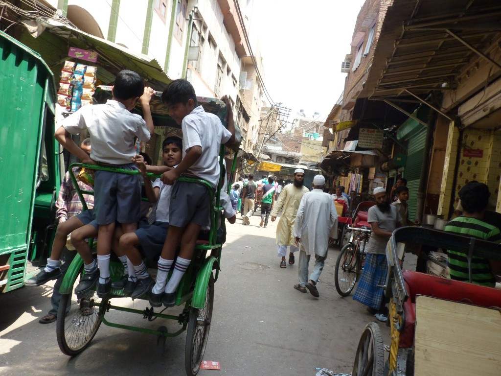 Children hang off the back of a rickshaw to come home from school